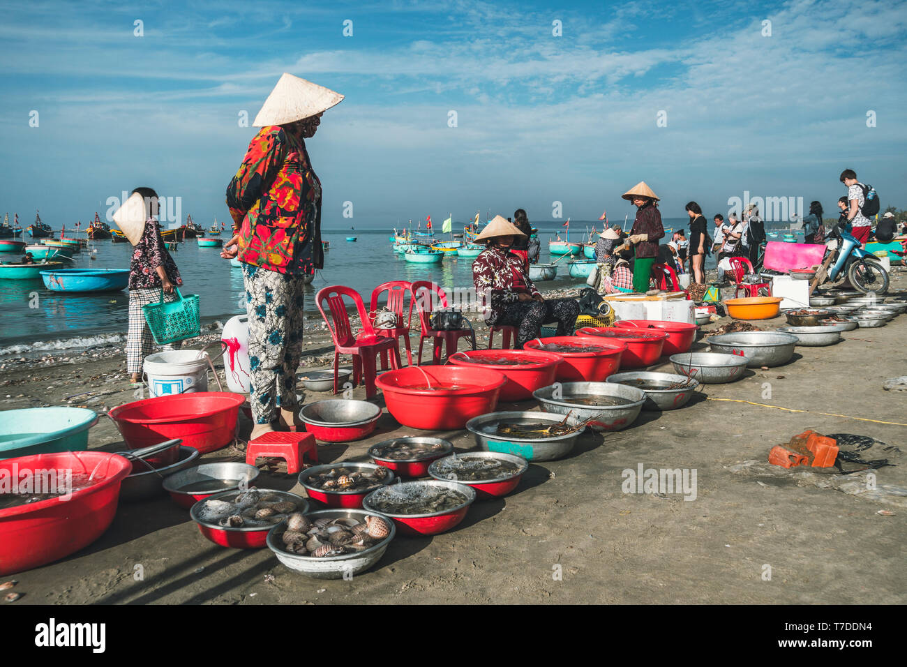 Traders sell fresh fish, crabs and other seafood on the dirty beach. Fishermen village in MUI ne. Vietnam. Mui Ne, Vietnam. 27.01.2019: - Stock Image