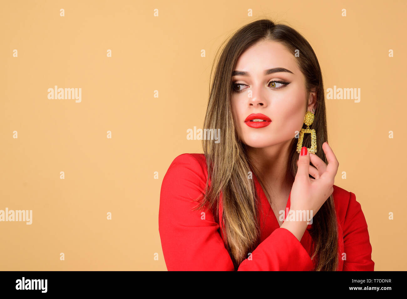 Jewelry shop. Girl model long hair demonstrating golden jewelry earrings. Expensive accessory. Fashionable jewelry. Impeccable makeup and perfect jewelry. Woman wear glamorous earrings. Fashion trend. - Stock Image
