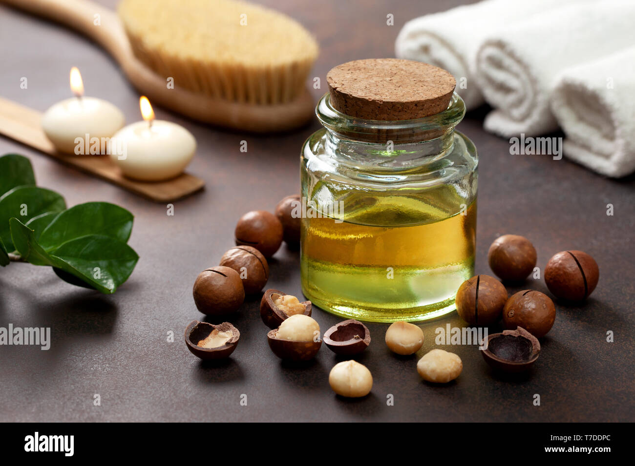 macadamia oil in a glass bottle, macadamia nuts, objects for spa on a brown background Stock Photo