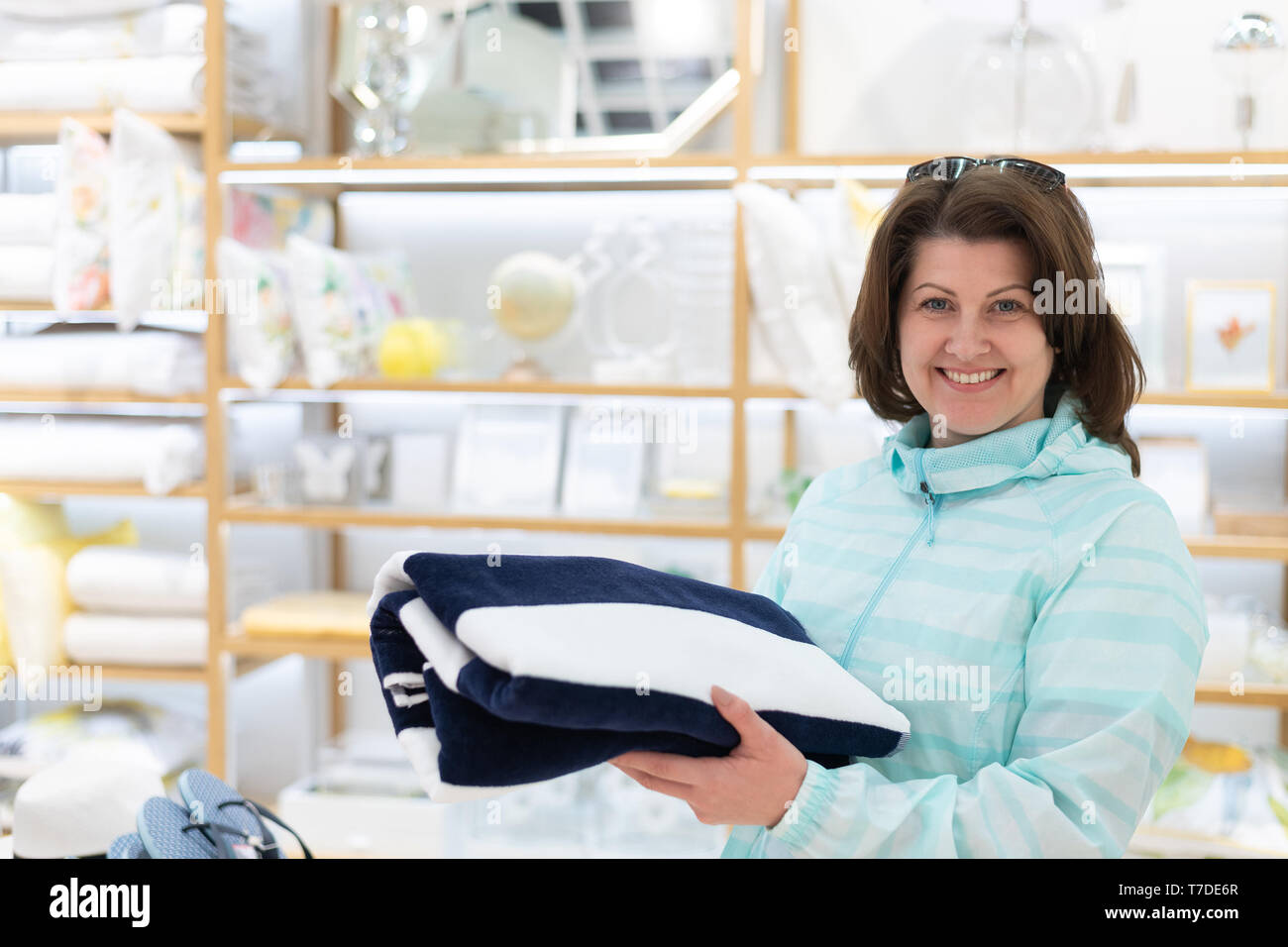 The woman chooses a towel in the store - Stock Image