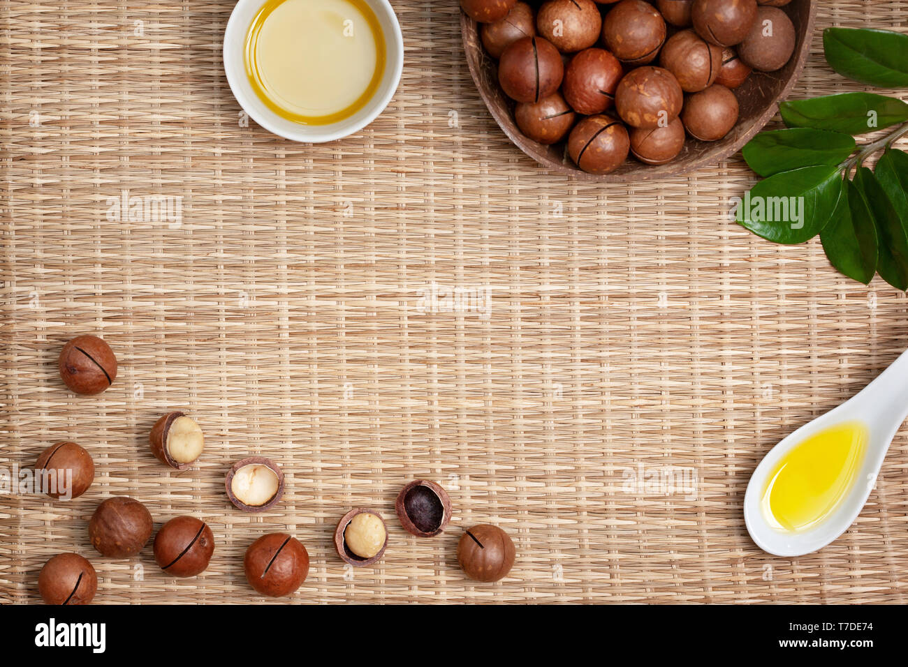 macadamia nuts in a bowl, macadamia oil in a white bowl on a straw (bamboo) background. view from above Stock Photo
