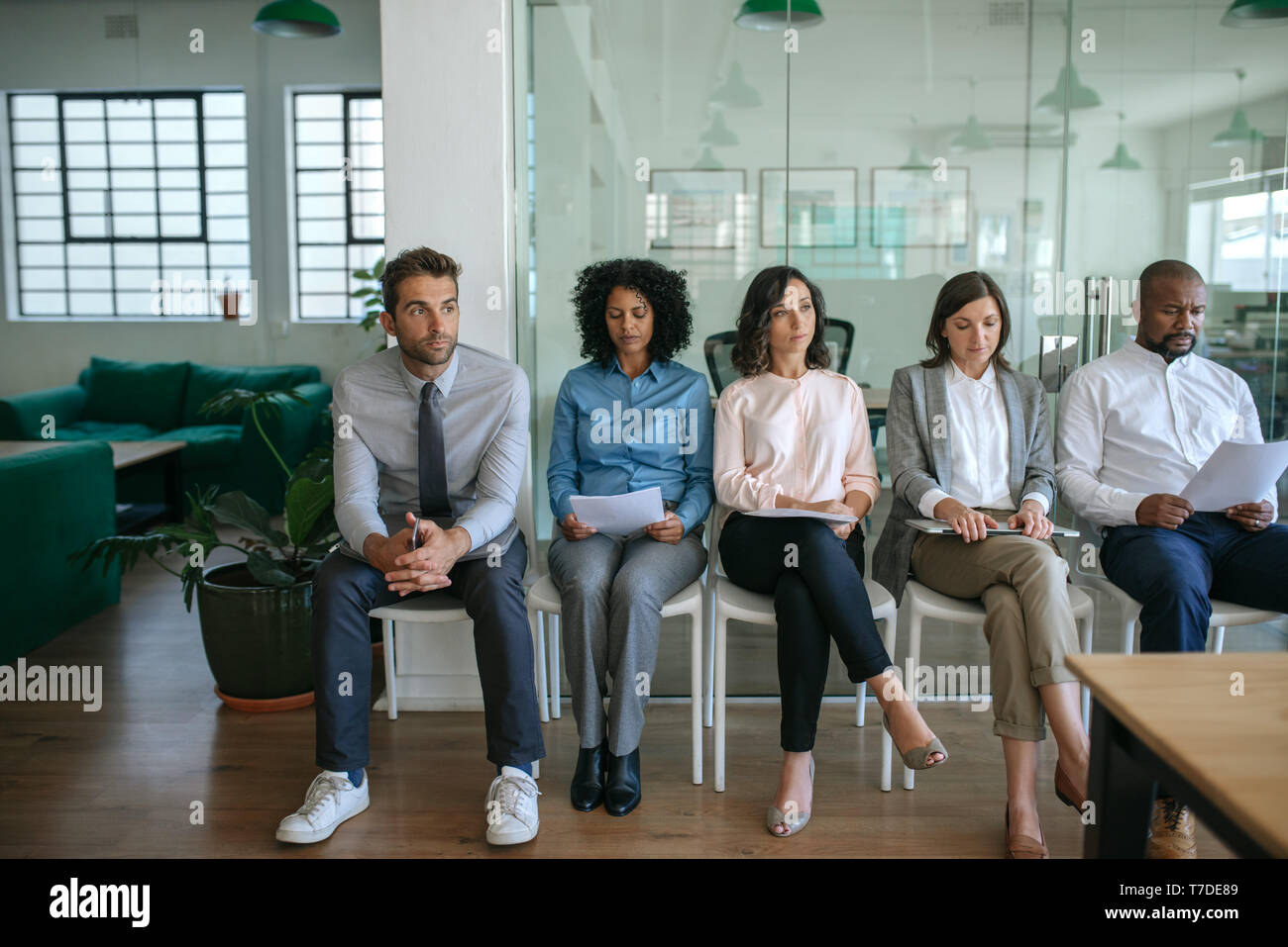 People waiting for their job interviews in an office - Stock Image