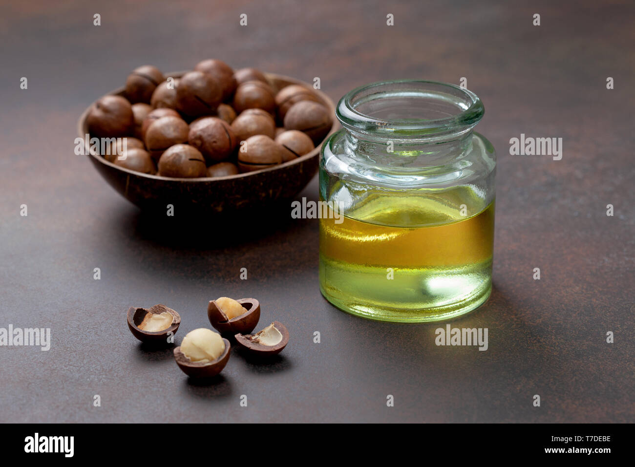 macadamia oil in a glass bottle, macadamia nuts on a brown background Stock Photo