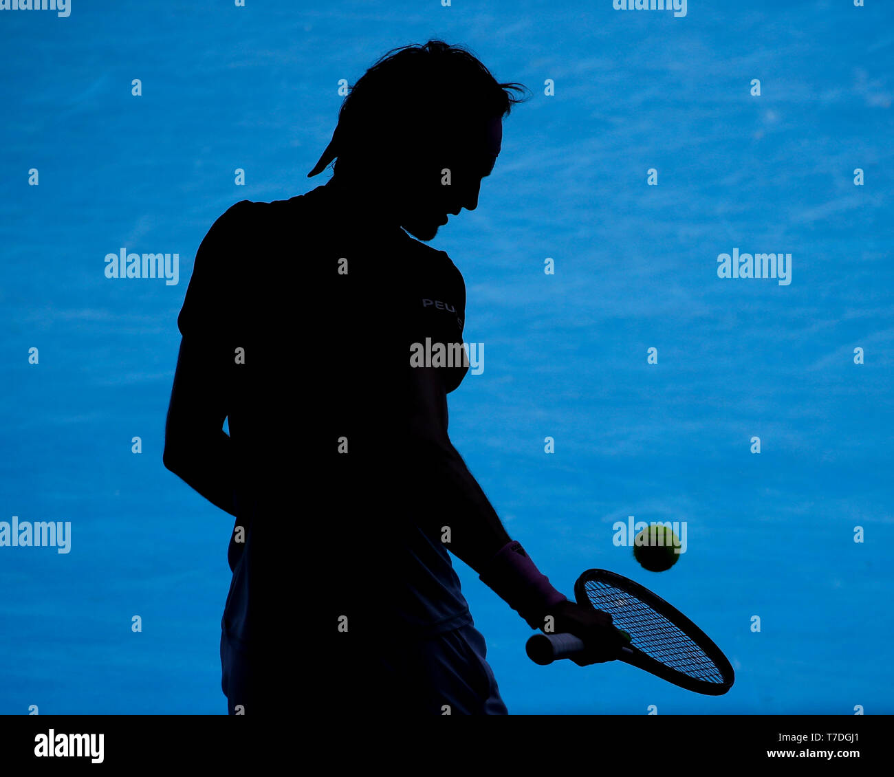 Silhouette of German tennis player Alexander Zverev standing with tennis ball and racquet during Australian Open 2019 tennis tournament, Melbourne Par - Stock Image