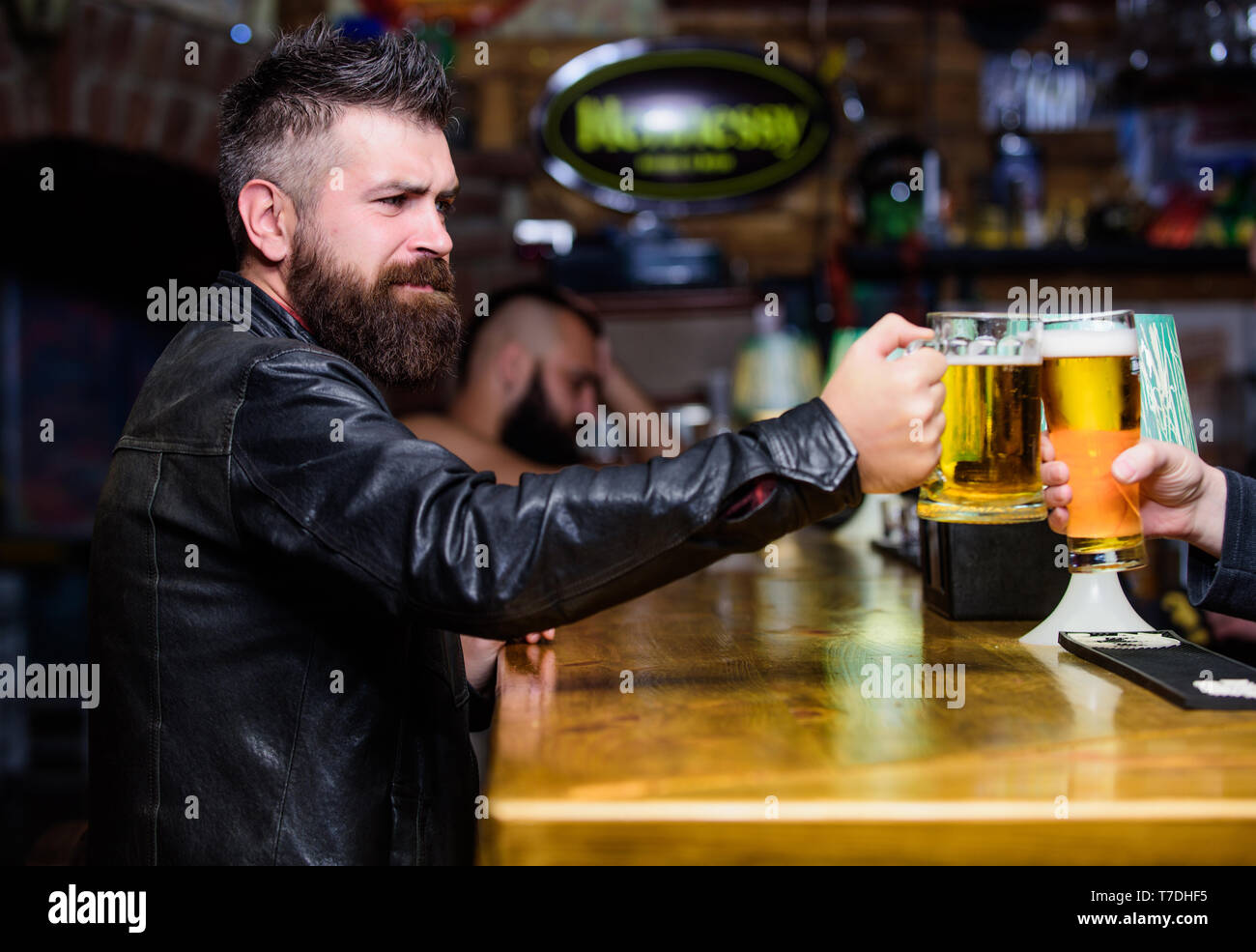 Cheers concept. Glasses with fresh lager draft beer with foam. Men hipster hold mugs filled with cold tasty beer in bar. Friday leisure tradition. Beer mugs at bar counter defocused background. - Stock Image
