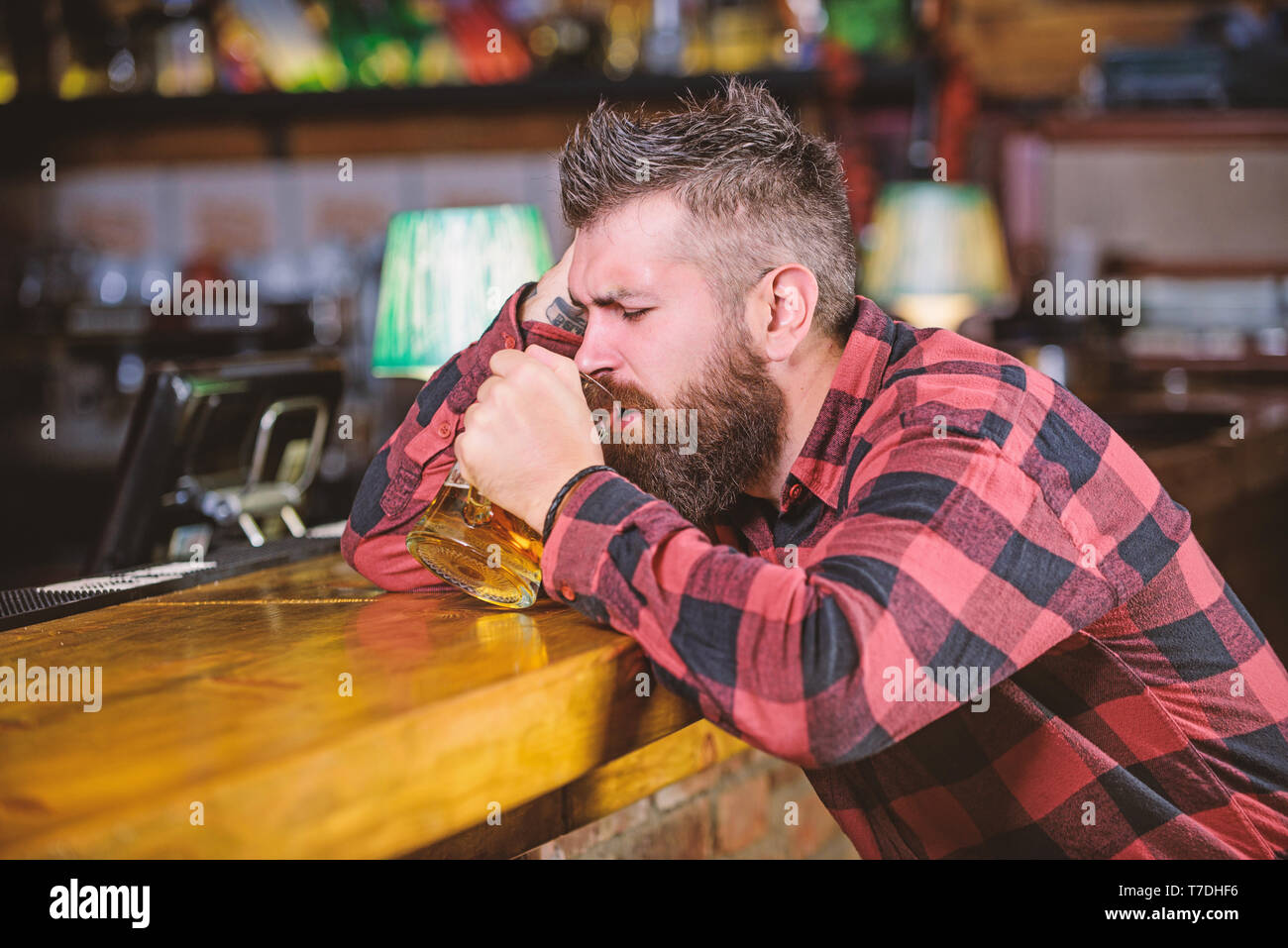 Man with beard spend leisure in dark bar. Brutal hipster bearded man sit at bar counter drink beer. Hipster relaxing at bar with beer. Order alcohol drink. Bar is relaxing place have drink and relax. - Stock Image