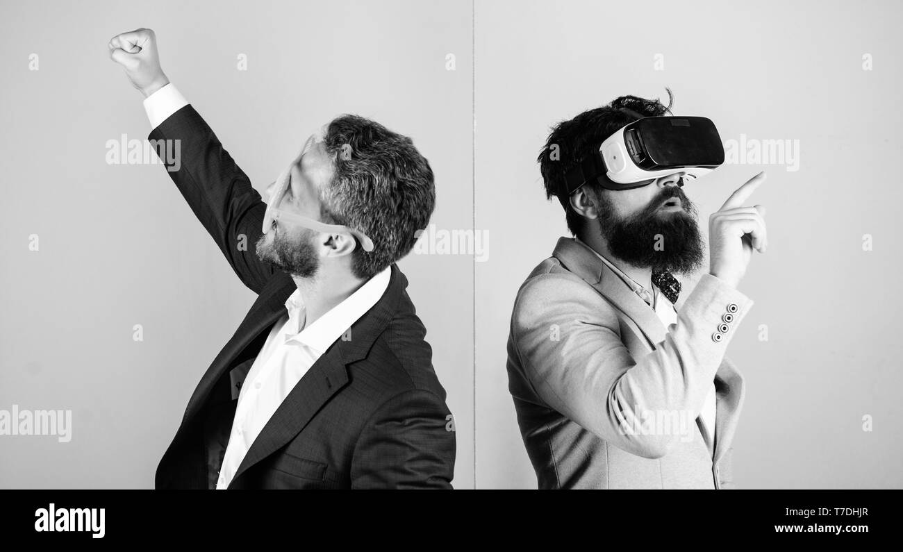 Business implement modern technology. Real fun and virtual alternative. Man with beard in VR glasses and louvered plastic accessory. Guy interact in virtual reality. Hipster exploring virtual reality. - Stock Image