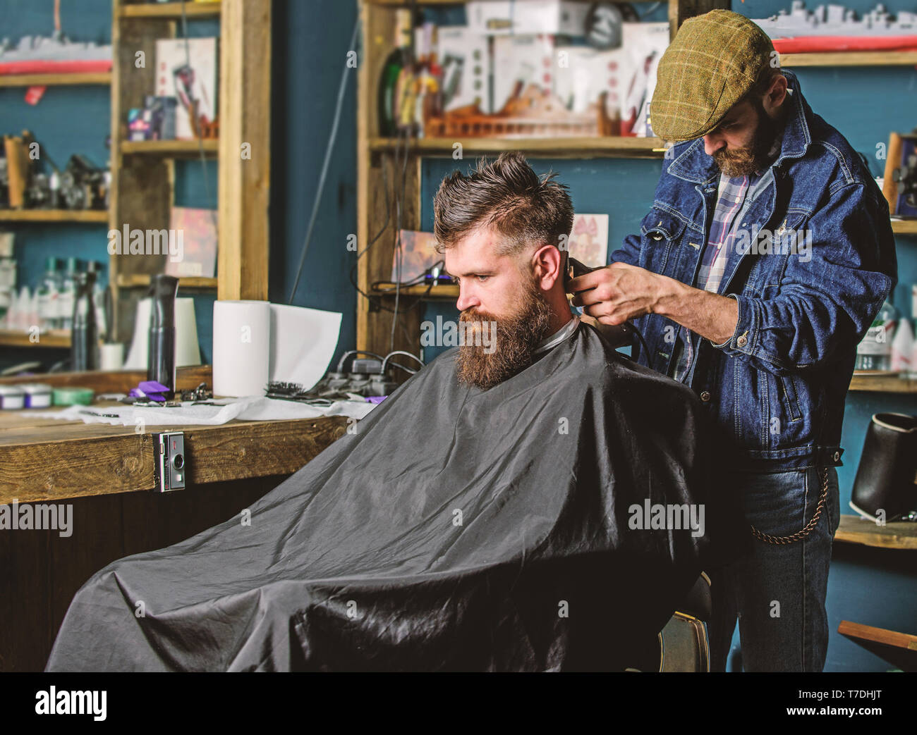 Barber with hair clipper works on haircut of bearded guy, retro barbershop background. Hipster hairstyle concept. Hipster client getting haircut. Barber with clipper trimming hair on nape of client. - Stock Image