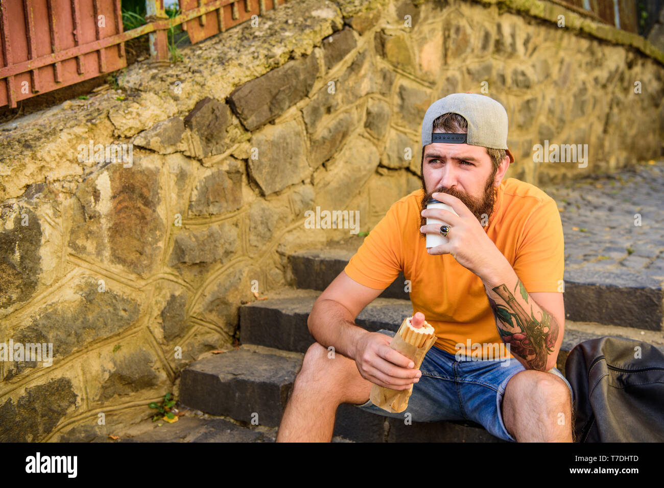 Man bearded enjoy quick snack. Street food so good. Urban lifestyle and unhealthy nutrition. Carefree hipster eat junk food while sit on stairs. Hungry man snack. Junk food. Guy eating hot dog. - Stock Image
