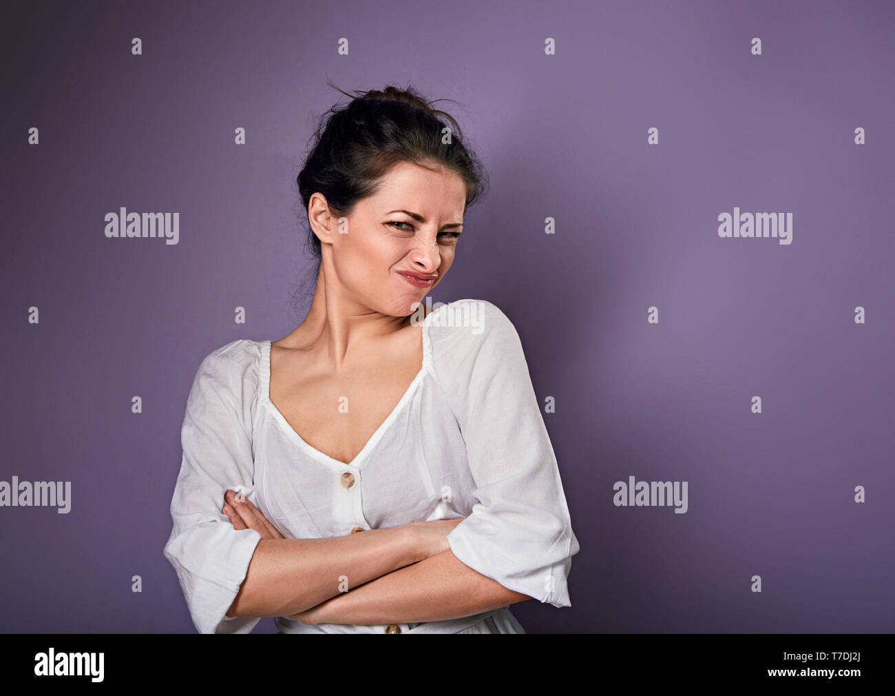 Beautiful unhappy woman in white shirt looking with disgust and grimacing the face on purple background with empty copy space - Stock Image