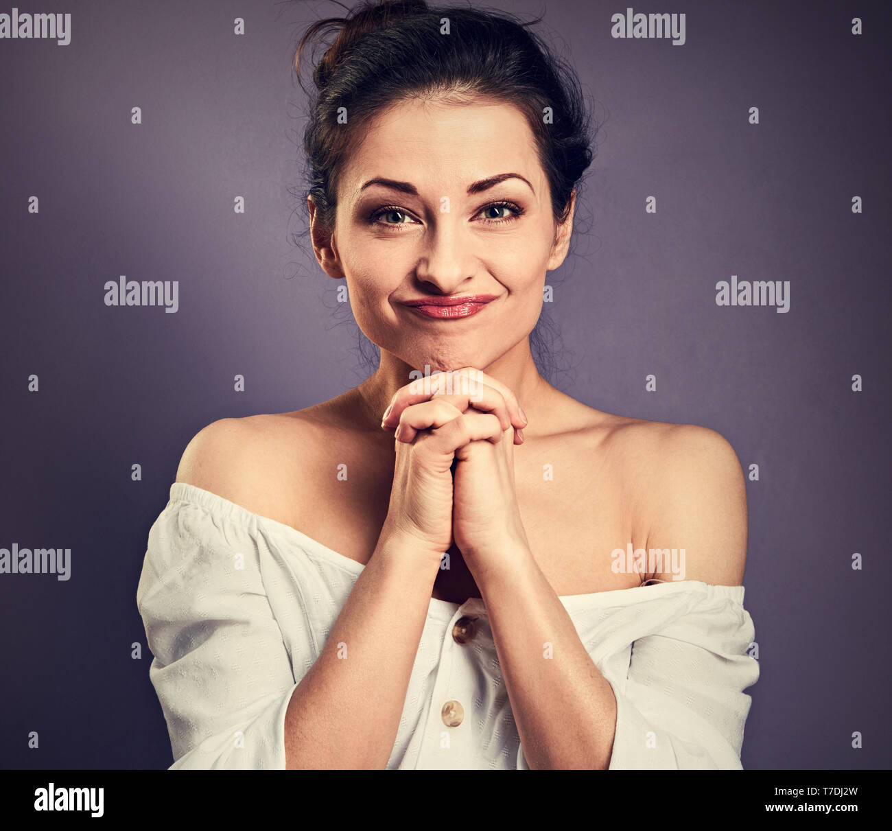 Beautiful excited fun grimacing woman in white shirt holding the hands under the face. Closeup portrait on empty purple copy space. Toned contrast vin - Stock Image