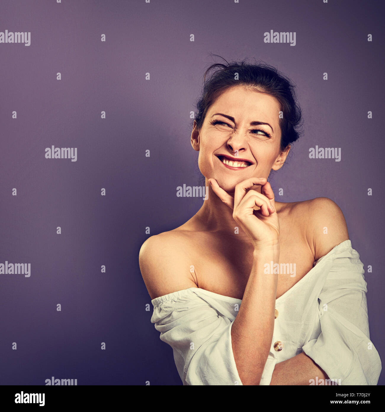 Beautiful positive grimacing fun woman with hand under the face thinking and looking up in white shirt on purple background with empty copy space. Ton - Stock Image