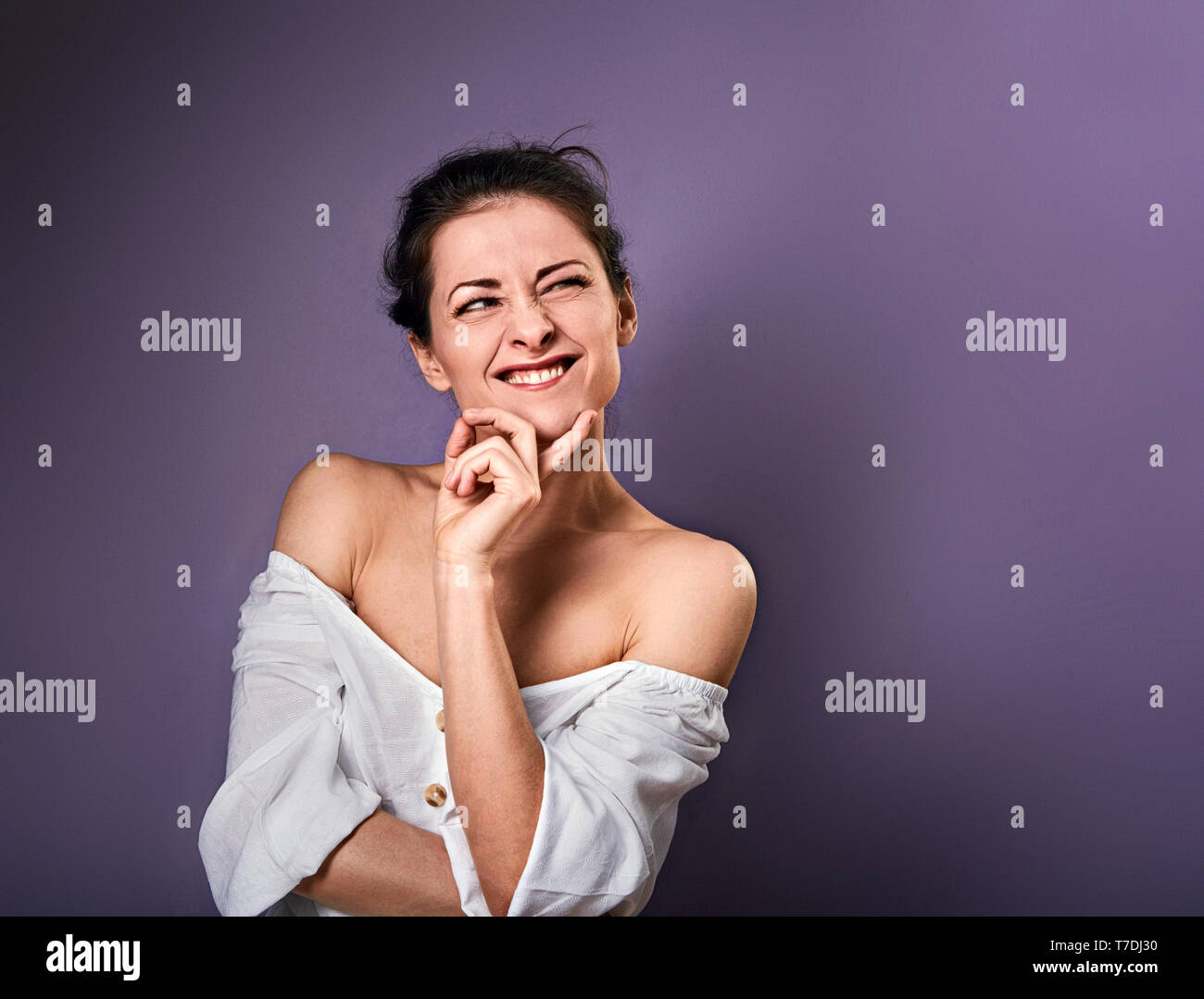Beautiful positive grimacing fun woman with hand under the face thinking and looking up in white shirt on purple background with empty copy space. - Stock Image