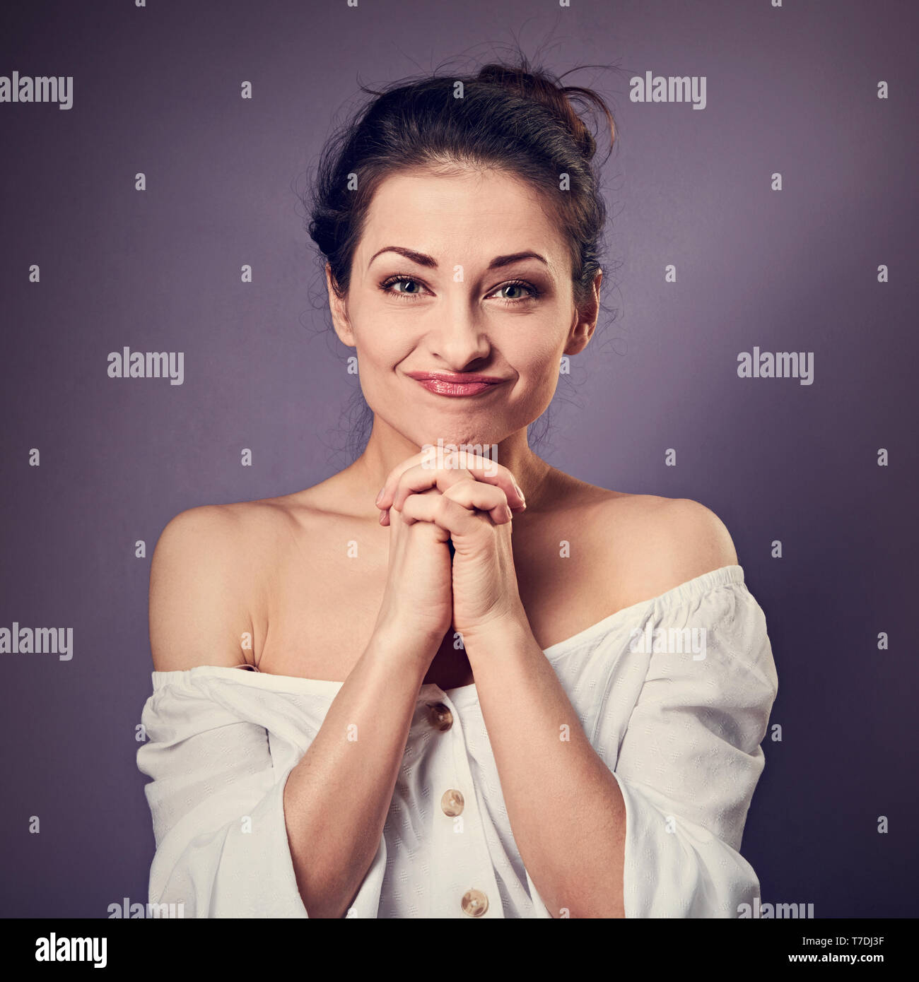 Beautiful excited fun grimacing woman in white shirt holding the hands under the face. Closeup toned portrait on empty purple copy space. - Stock Image