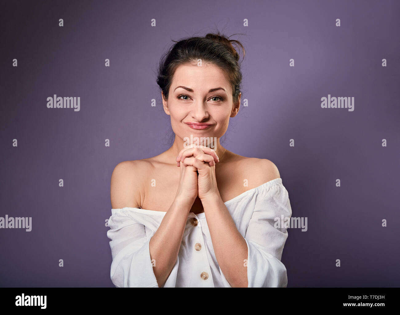 Beautiful excited fun grimacing woman in white shirt holding the hands under the face. Closeup portrait on empty purple copy space. - Stock Image