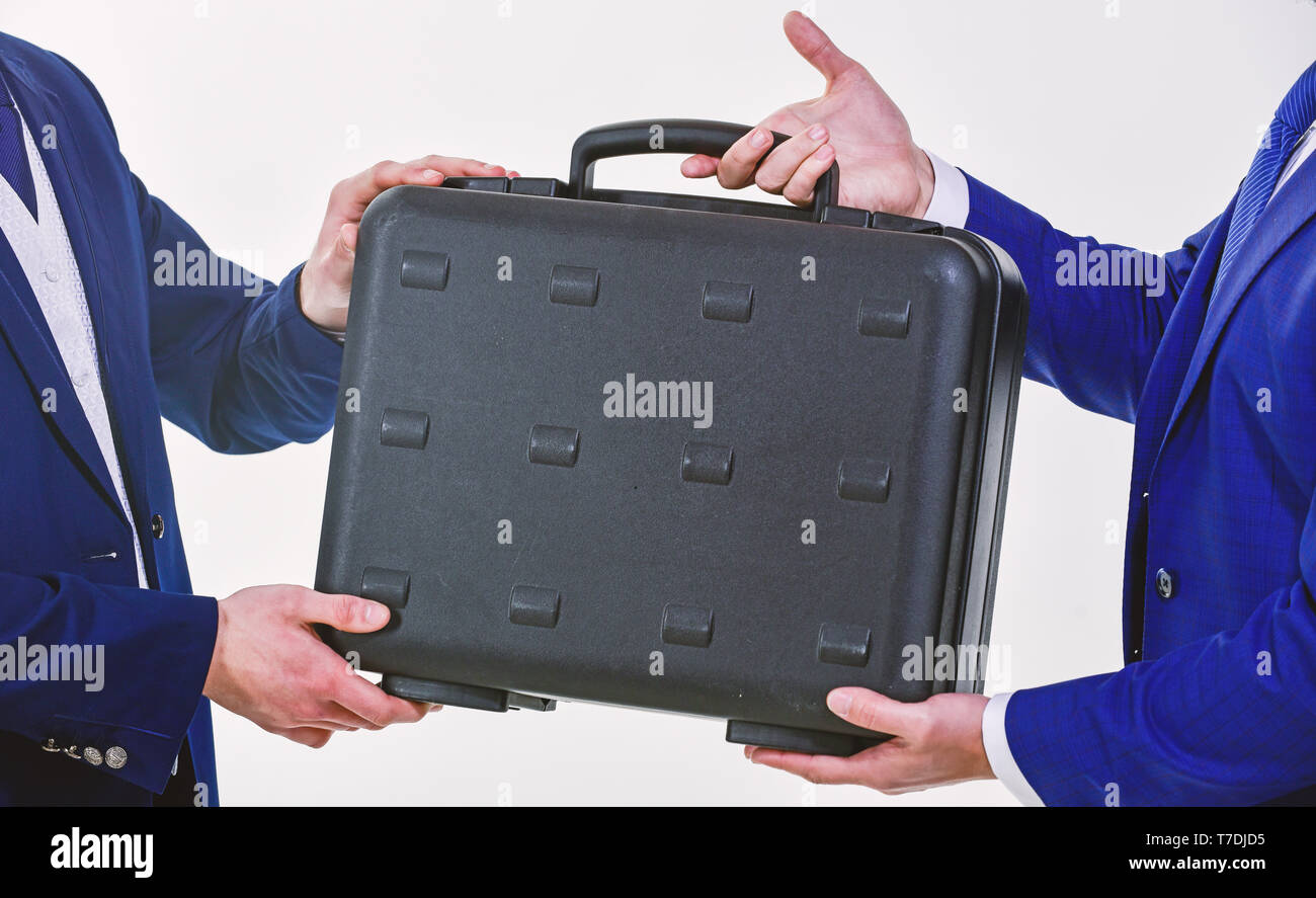Hands give briefcase for exchange or offer bribe. Business transfer concept. Male hand hold briefcase. Handover of case in hands of business partners. Handover of illegal goods. Illegal deal handover. - Stock Image