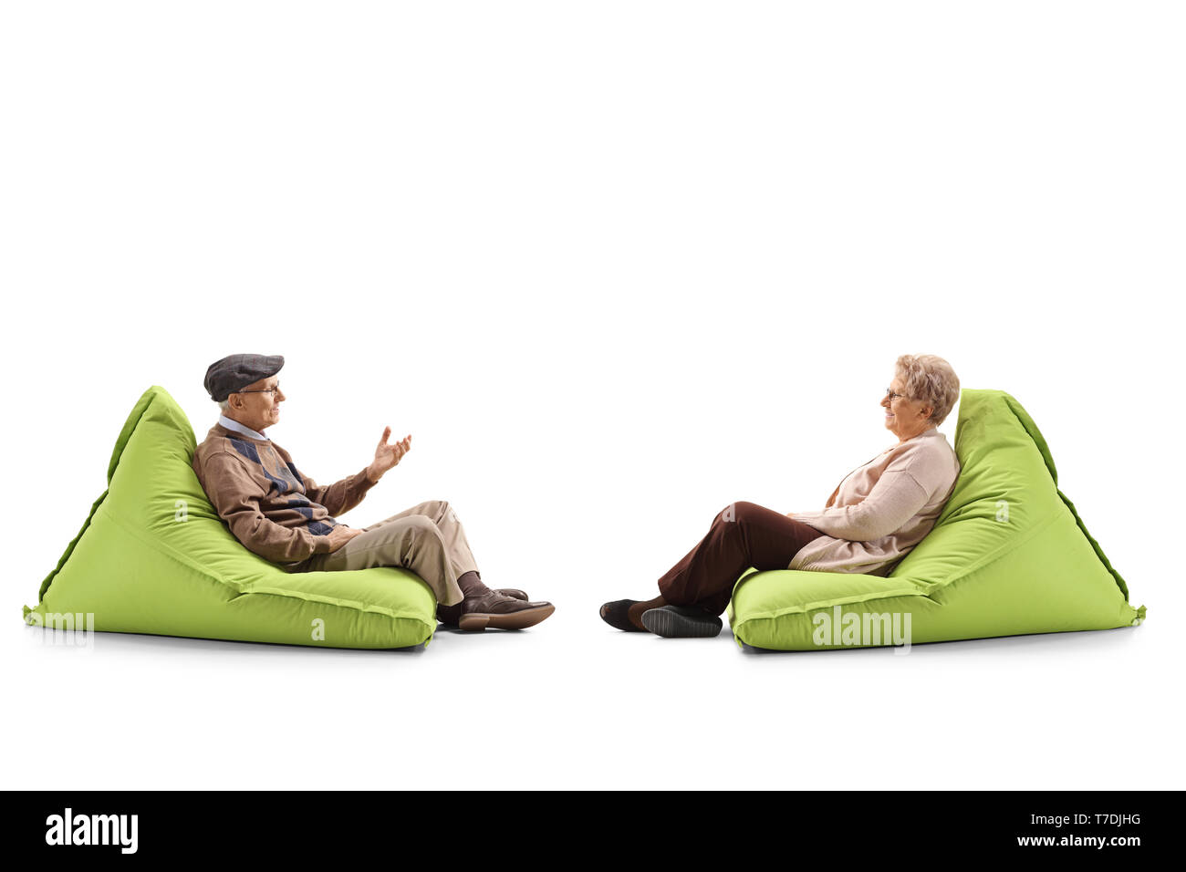 Full length profile shot of an elderly couple sitting on a bean bag armchairs and talking isolated on white background - Stock Image