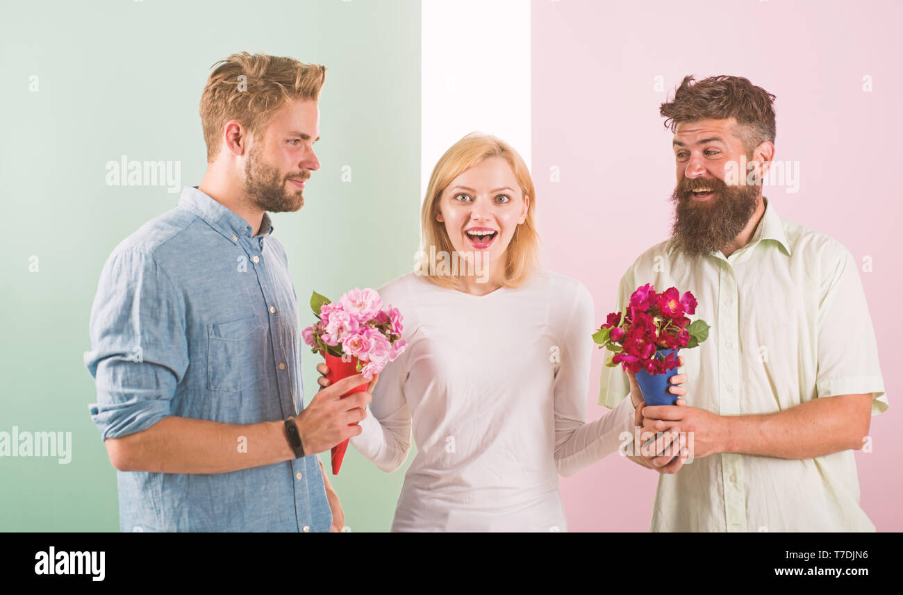 Girl popular receive lot men attention. Woman smiling can not choose partner, grabs both bouquets. Girl happy likes gifts. Love triangle. Men competitors with bouquets flowers try conquer girl. - Stock Image
