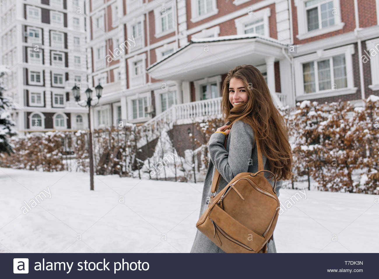 Long-haired woman with brown backpack walking past beautiful building in winter day. Outdoor portrait of wonderful brunette girl looking over shoulder while exploring city in snowy morning.. - Stock Image