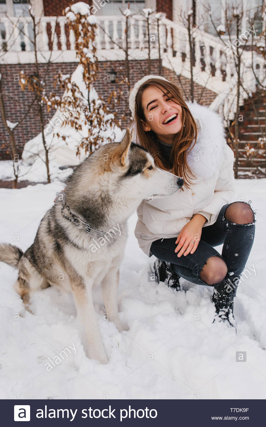 Fashionable joyful young woman having fun with lovely husky dog in snow on the street. True emotions, happy moments in winter time, smiling, expressing positivity, waiting for christmas - Stock Image