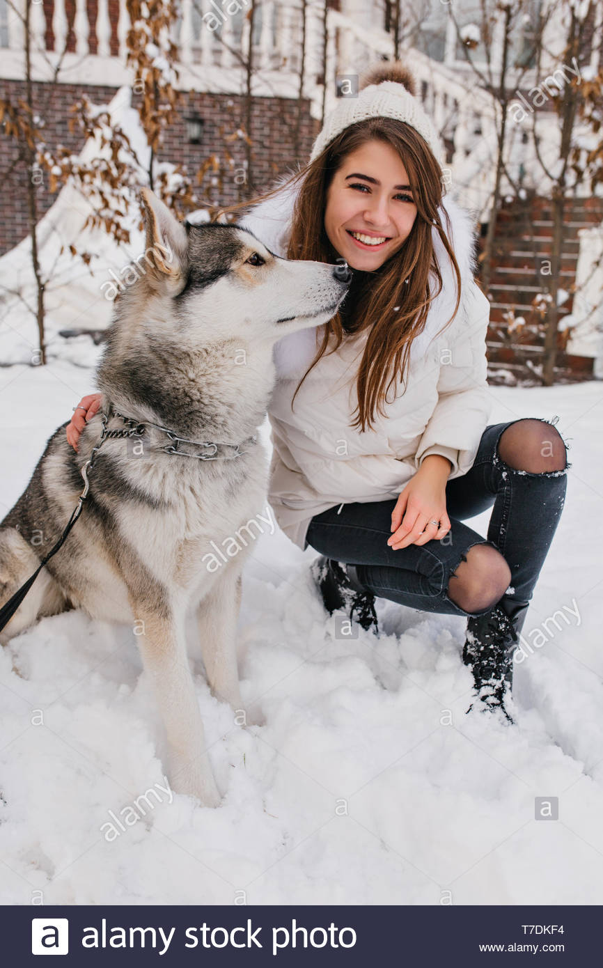 Real friendship of amazing young woman enjoying winter time with husky dog. Pretty charming girl enjoying snow outdoor with home pet. Happy moments, waiting for christmas, true emotions, smiling - Stock Image
