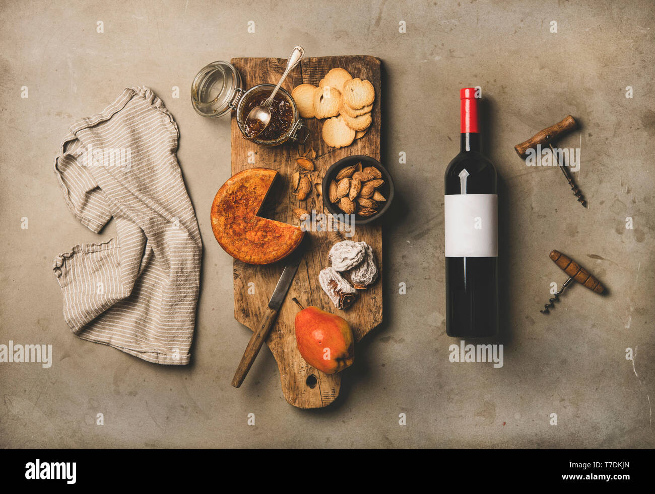 Wine and snack set. Flat-lay of wine bottle with blank label, vintage corkscrews, linen towel and cheese and appetizers board over concrete background - Stock Image