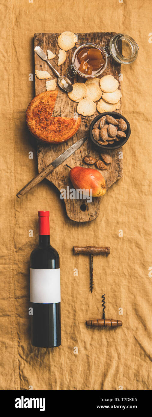 Wine and snack set. Flat-lay of wine bottle with blank label, vintage corkscrews and cheese and appetizers board over dusty yellow linen tablecloth, t - Stock Image