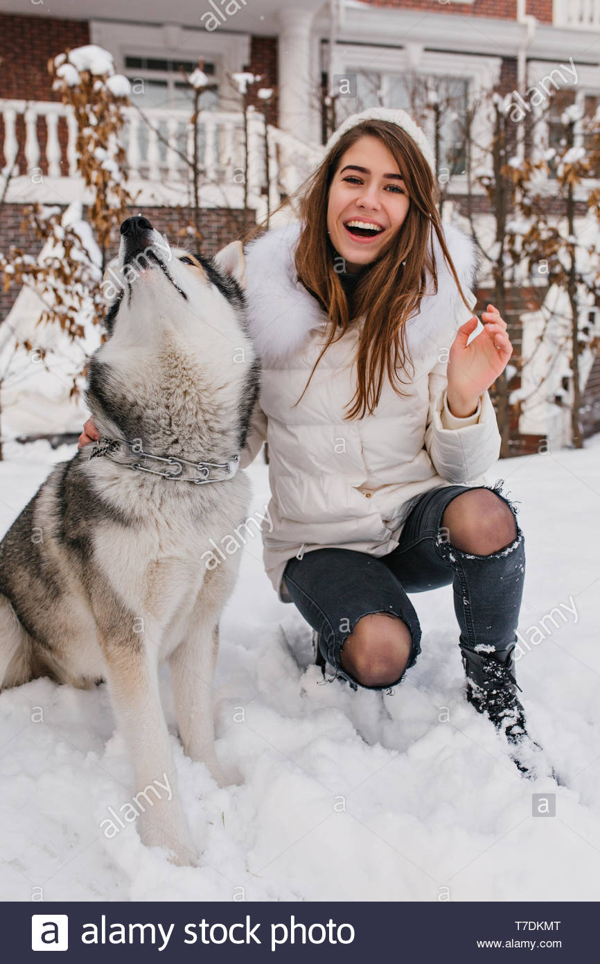 Joyful pretty girl in winter clothes playing with husky dog in snow. Fashionable young woman enjoying cold winter weather with domestic pet. Real friendshop, smiling, having fun, christmas mood - Stock Image