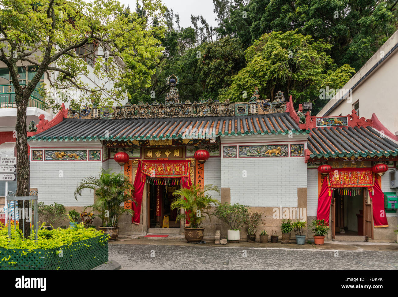 Hong Kong, China - March 7, 2019: Tai O Fishing village. Frontal view of Kwan Tai Taoist temple with white wall and red doorways. Extensive roof decor - Stock Image