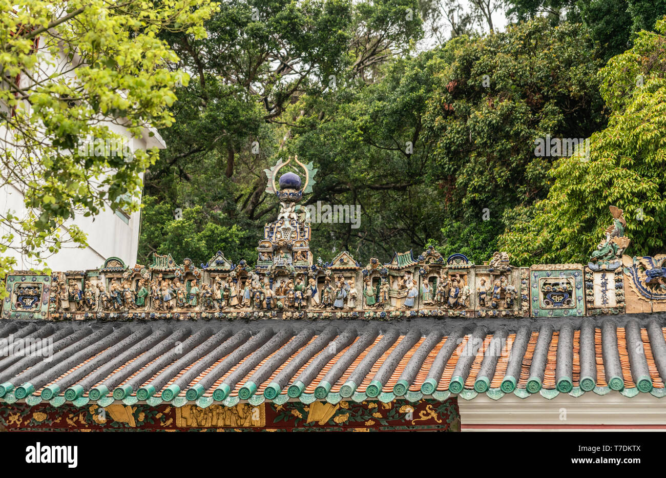 Hong Kong, China - March 7, 2019: Tai O Fishing village. Extensive statue decorations on roof of Kwan Tai Taoist temple. Surrounded by green foliage. - Stock Image