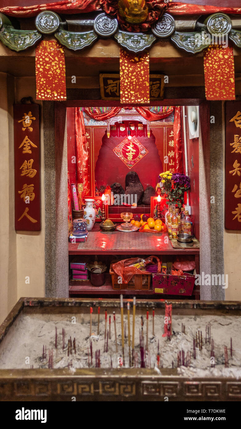 Hong Kong, China - March 7, 2019: Tai O Fishing village. Idol altar inside small Taoist shrine at east entrance to the village. Red as dominant color, - Stock Image
