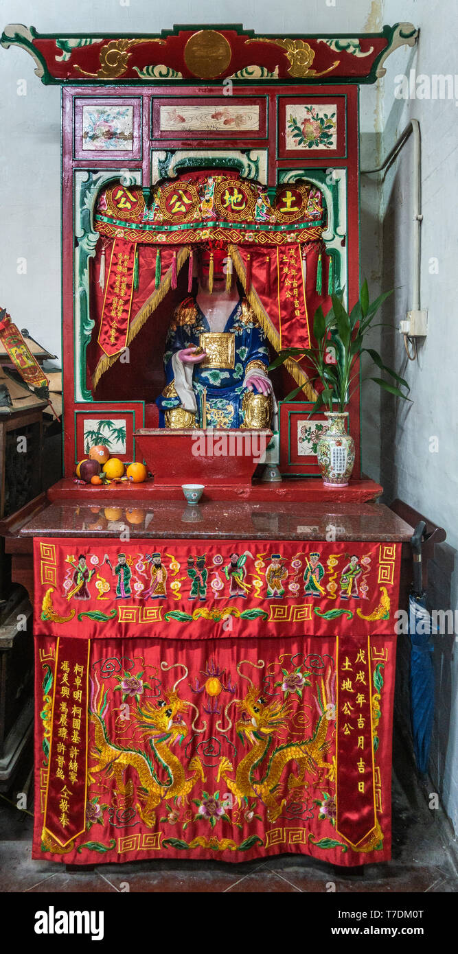 Hong Kong, China - March 7, 2019: Tai O Fishing village. Closeup of side shrine with idol captured in red and gold at Kwan Tai Taoist temple. Deity we - Stock Image