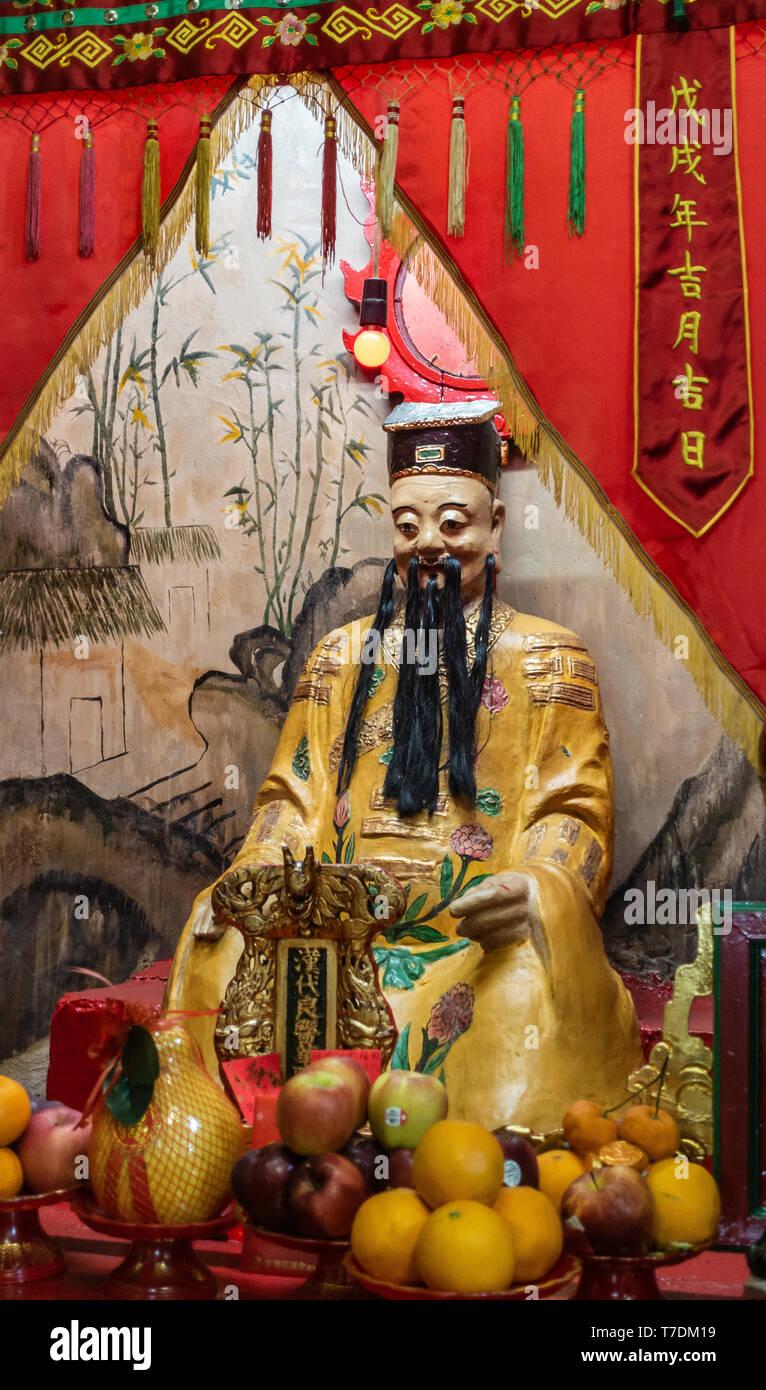 Hong Kong, China - March 7, 2019: Tai O Fishing village. Closeup of God of Medicine at Kwan Tai Taoist temple. Wears yellow dress and sits behind whit - Stock Image