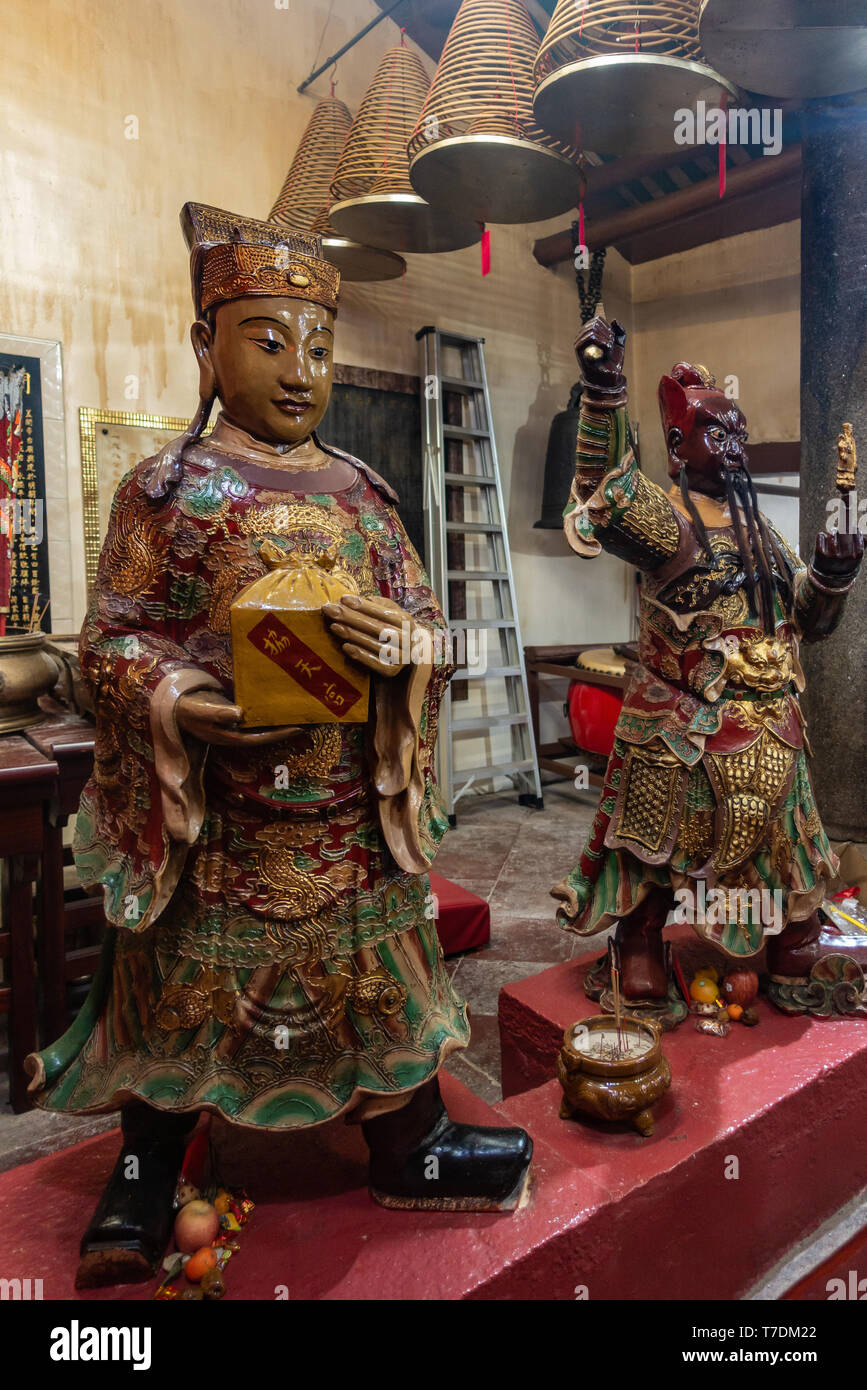 Hong Kong, China - March 7, 2019: Tai O Fishing village. Two life-size statues of fierce guards and gift bringers at Kwan Tai Taoist temple. - Stock Image