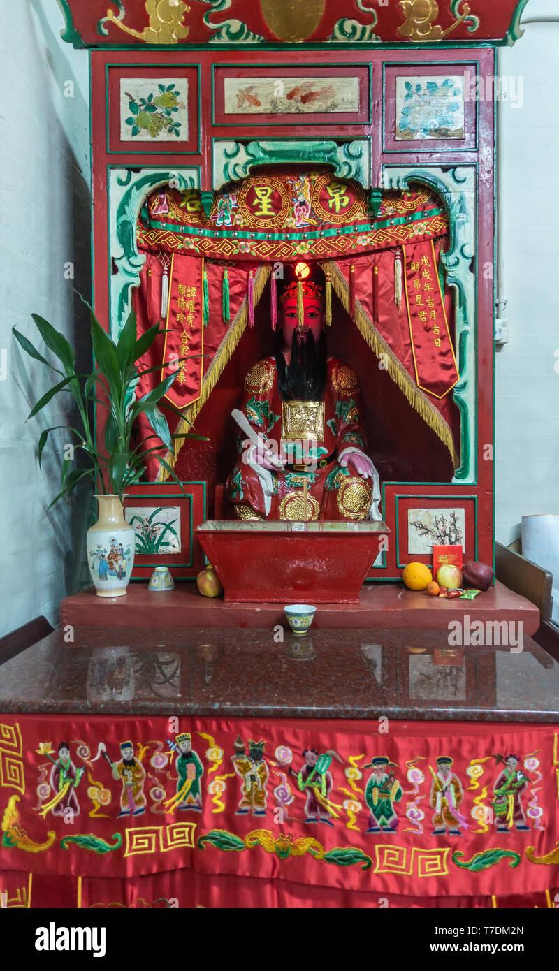 Hong Kong, China - March 7, 2019: Tai O Fishing village. Closeup of side shrine at Kwan Tai Taoist temple. dominant reds and gold. - Stock Image