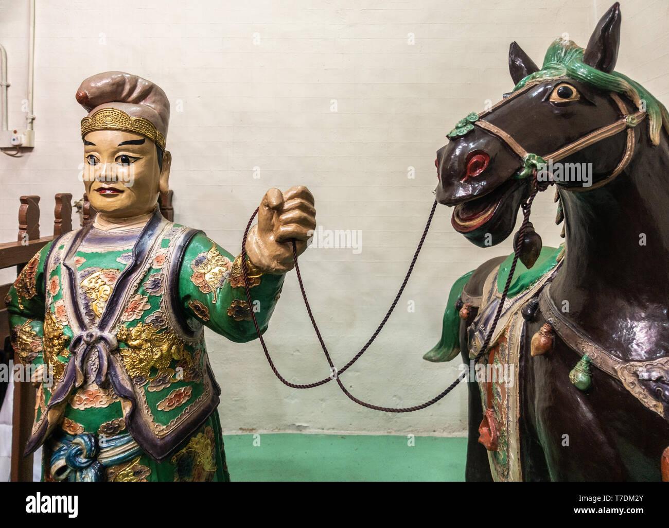 Hong Kong, China - March 7, 2019: Tai O Fishing village. Closeup of man with horse statue at Kwan Tai Taoist temple. - Stock Image