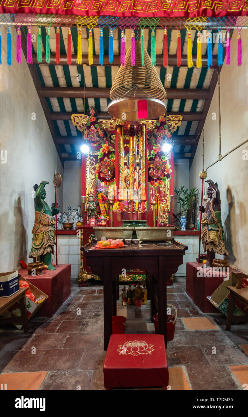 Hong Kong, China - March 7, 2019: Tai O Fishing village. God of sea altar partly hidden by garlands in front at Kwan Tai Taoist temple. Mainly reds an - Stock Image