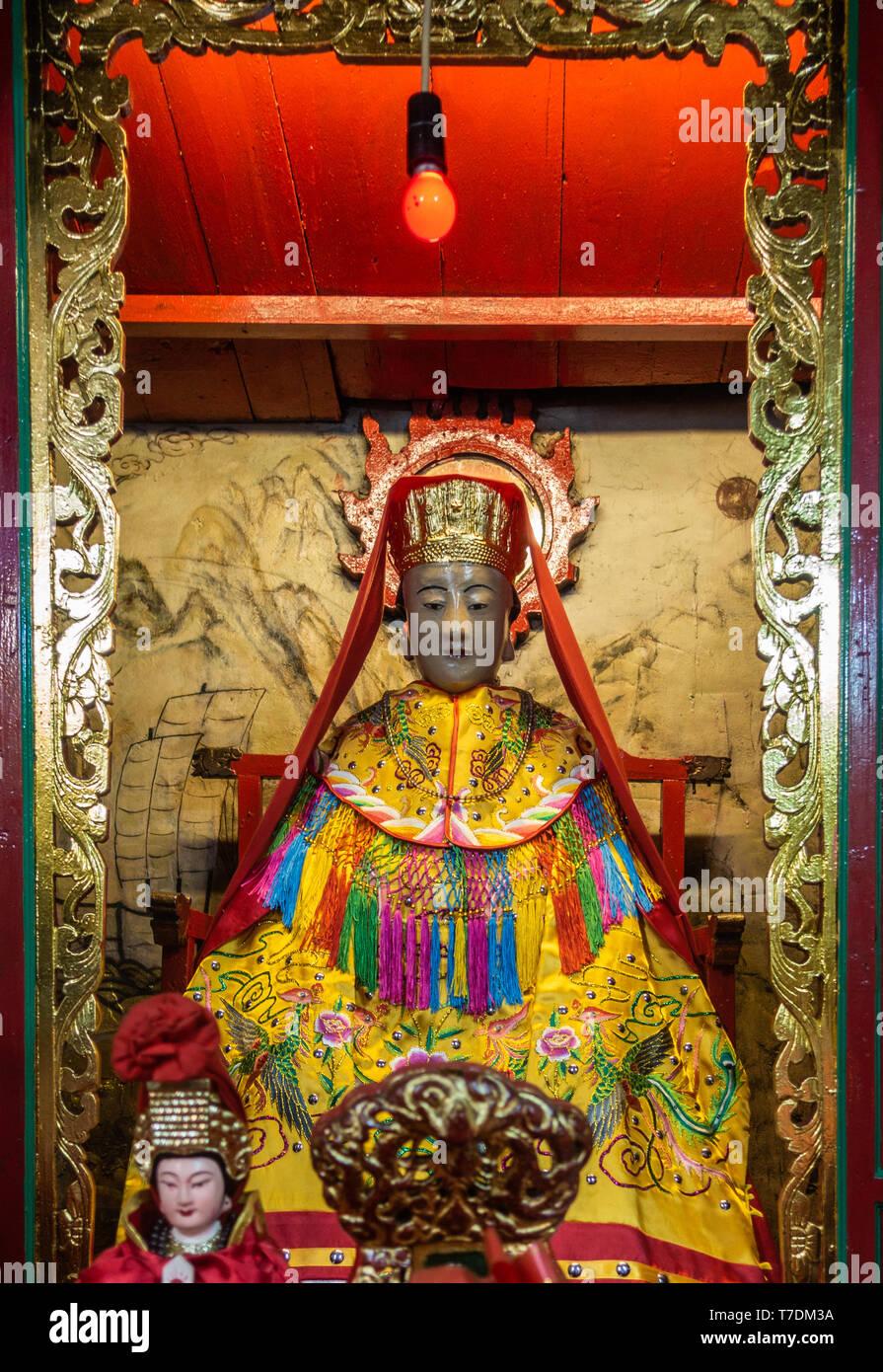 Hong Kong, China - March 7, 2019: Tai O Fishing village. Closeup of God of Sea at Kwan Tai Taoist temple. Wears yellow dress, colorful decorations, re - Stock Image