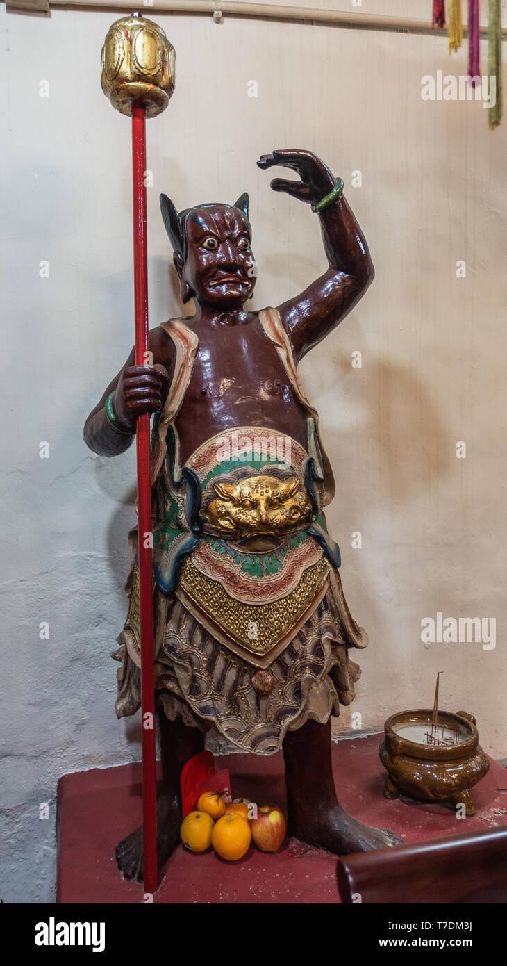 Hong Kong, China - March 7, 2019: Tai O Fishing village. Closeup of fierce-looking brown guardian in God of Sea shrine at Kwan Tai Taoist temple. Gray - Stock Image