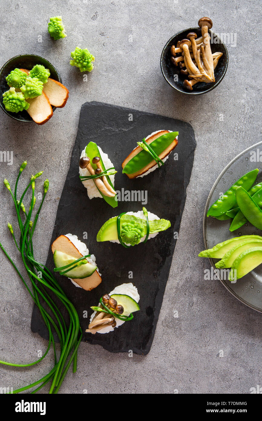 Springlike vegan nigiri sushi with smoked tofu, mushrooms and vegetables on white marble board over grey concrete background - Stock Image