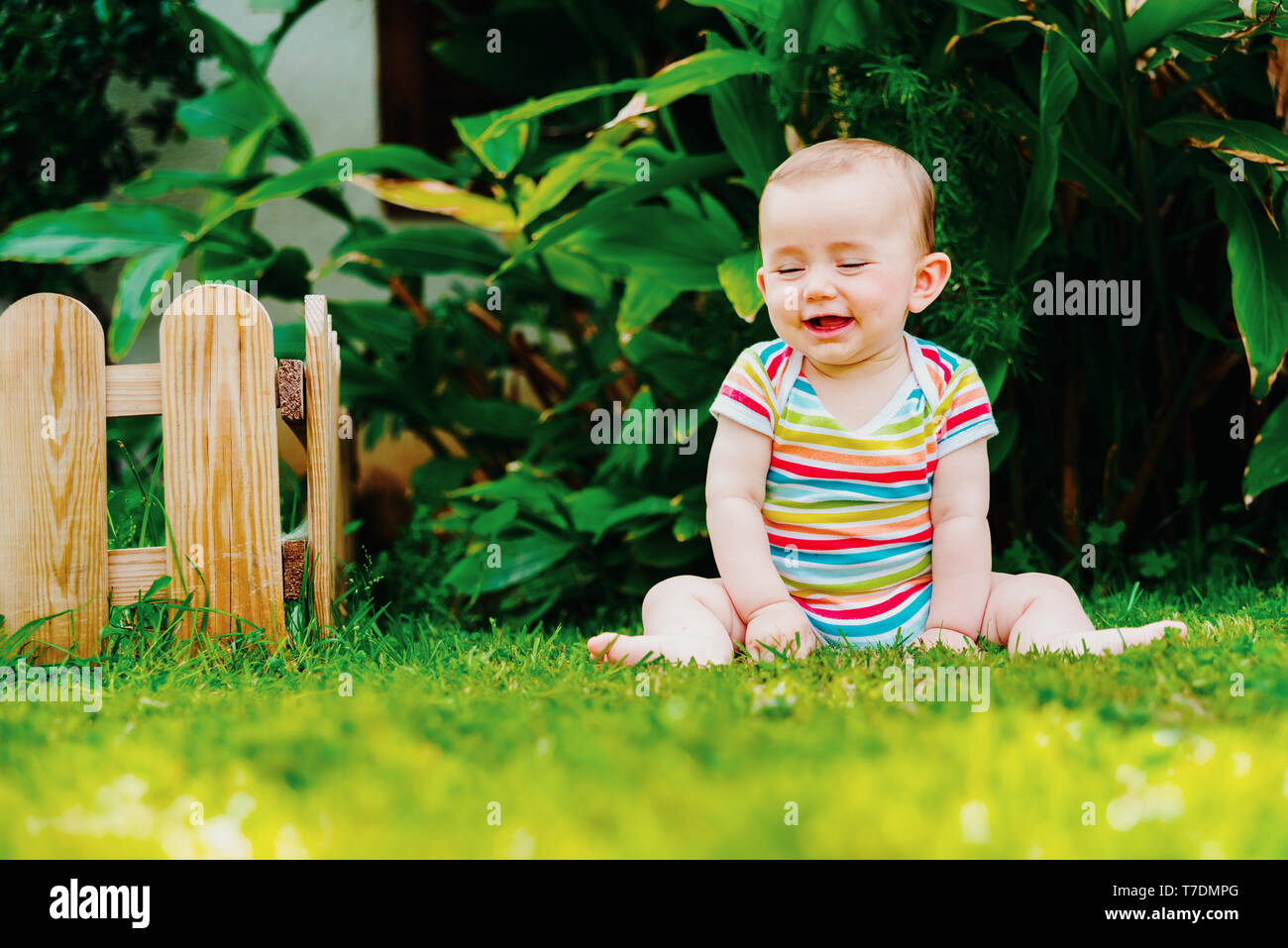 Lovely baby sitting on the grass laughing loudly. - Stock Image