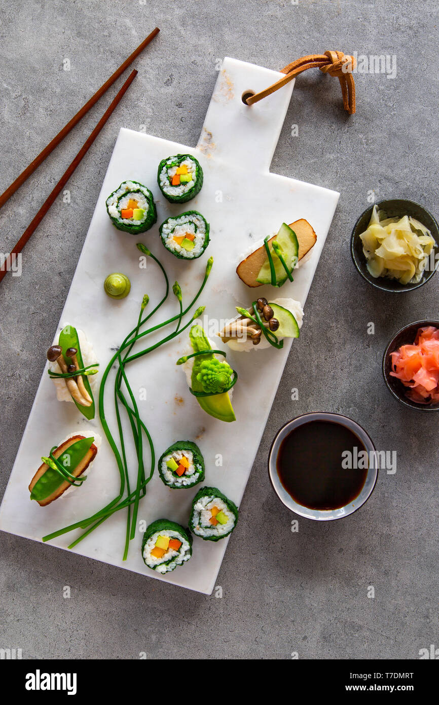 Springlike vegan maki and nigiri sushi with smoked tofu, mushrooms, fresh fruit and vegetables on white marble board over grey concrete background - Stock Image