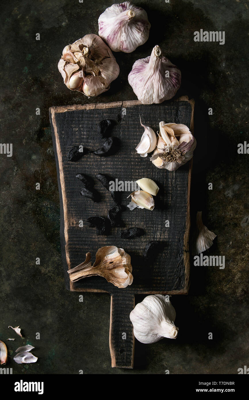 Variety of fresh organic garlic bulbs whole and peeled and cloves of black fermented garlic on wooden chopping board over dark metal background. Flat  Stock Photo