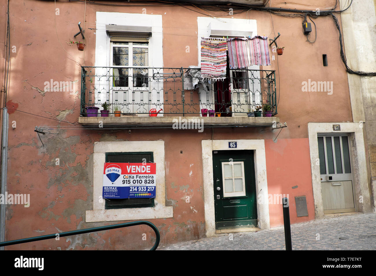 Exterior view of a for sale vende sign on a traditional house in old town with laundry outside Alfama Lisbon Portugal Europe EU  KATHY DEWITT - Stock Image