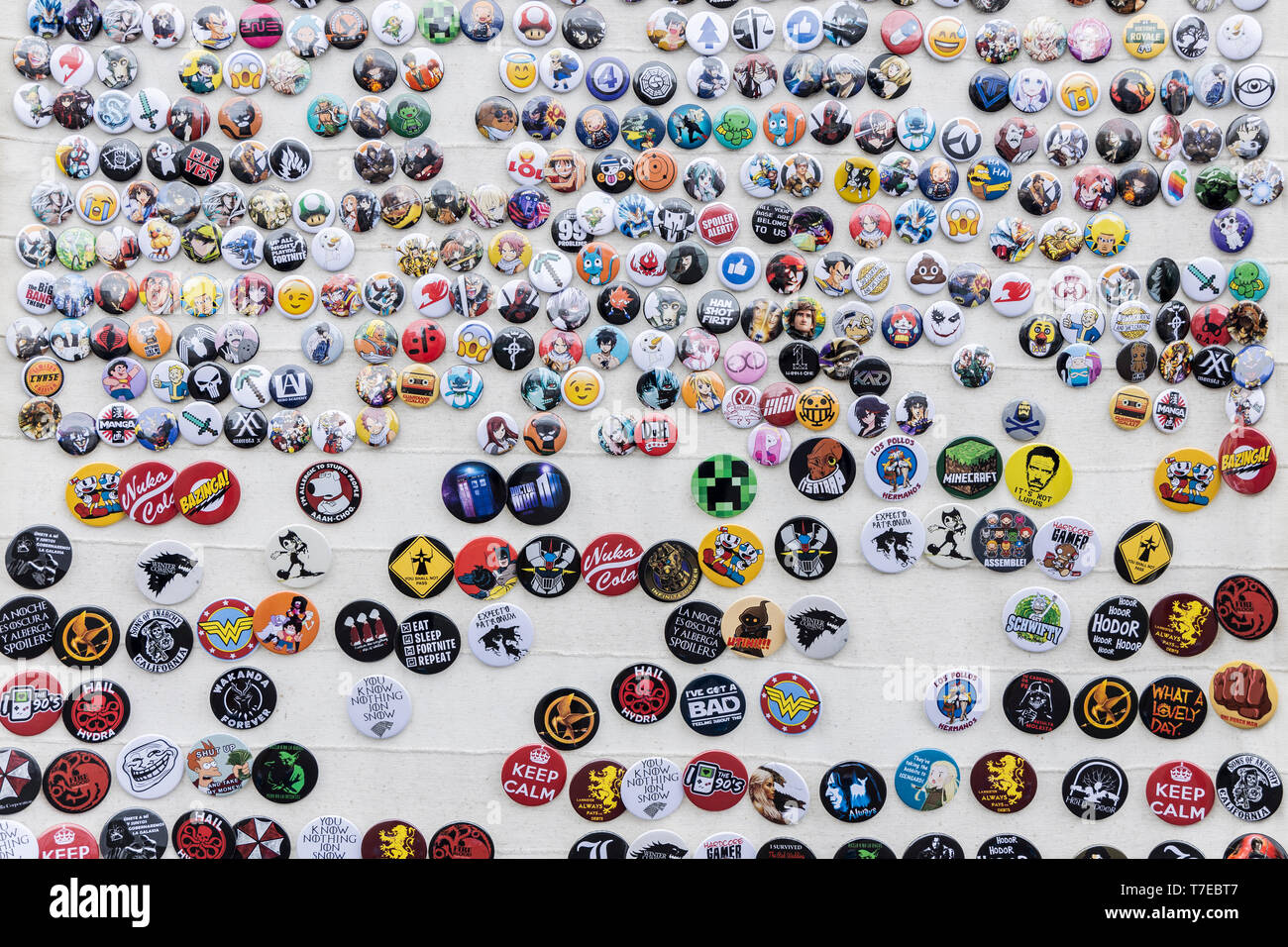 Wall of badges depicting cartoon and SciFi characters and slogans in english and Spanish - Stock Image
