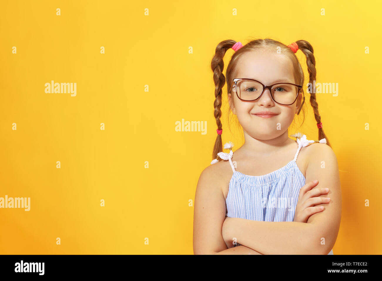 5589b50f170c Portrait of a funny little girl of preschool child with glasses on a yellow  background.