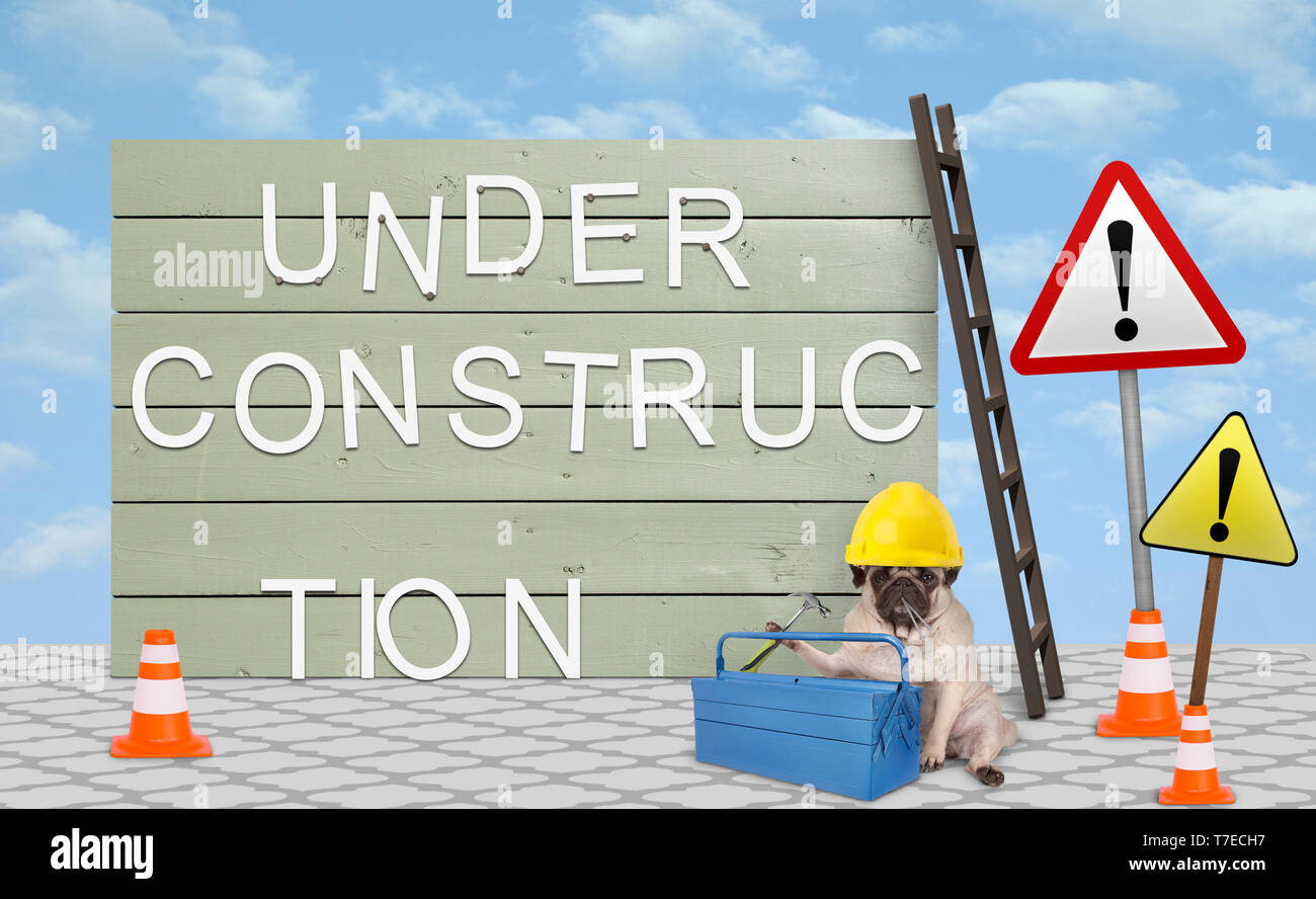 cute repairman pug puppy dog with yellow safety helmet, sitting down next to wooden board sign, with text under construction Stock Photo