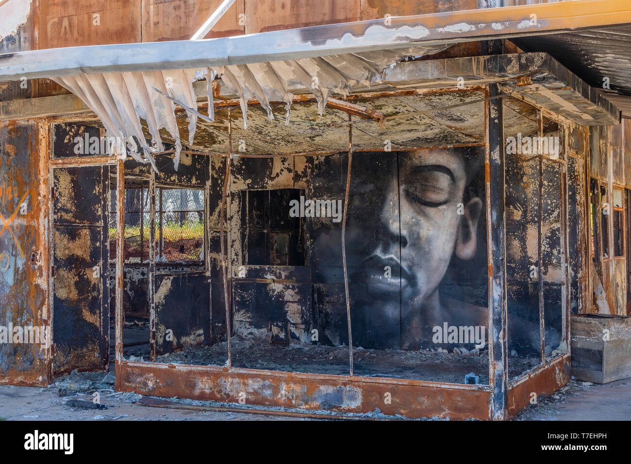 A building gutted by wildfire has a large face painted on an inside wall, looking out to the street, in the town of Paradise, California the site of t - Stock Image