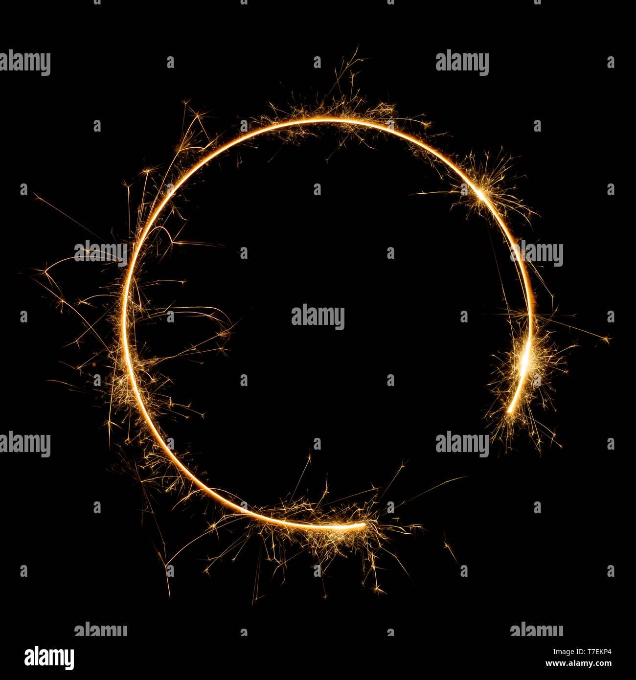 Burning bengal fire sparkler round letter o number zero, long exposure. Burning sparklers isolated on black. - Stock Image