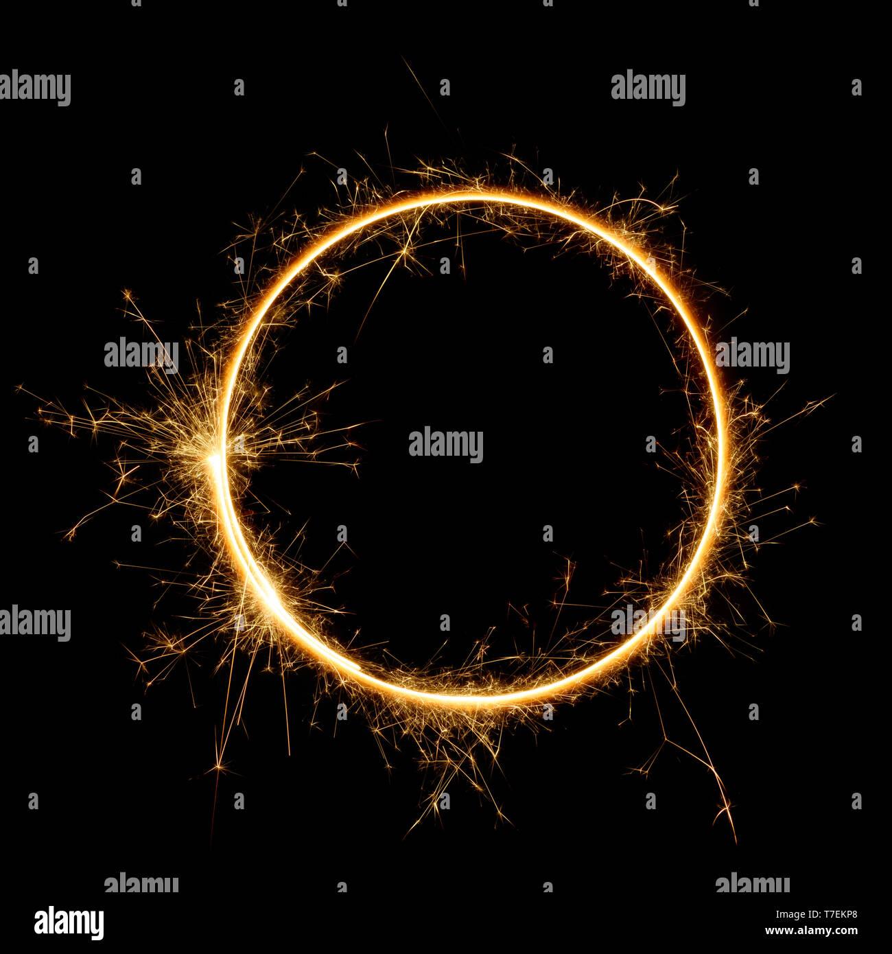 Sparkler circle shape. Burning bengal fire round letter o number zero, long exposure. Burning sparklers isolated on black. - Stock Image